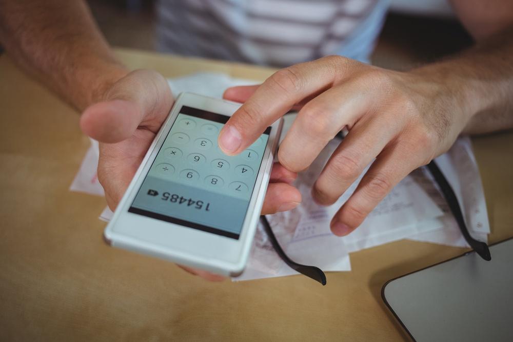 Man calculating bills on mobile phone